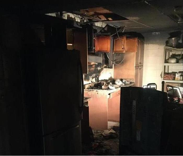 A kitchen damaged by fire, part of the ceiling collapsed