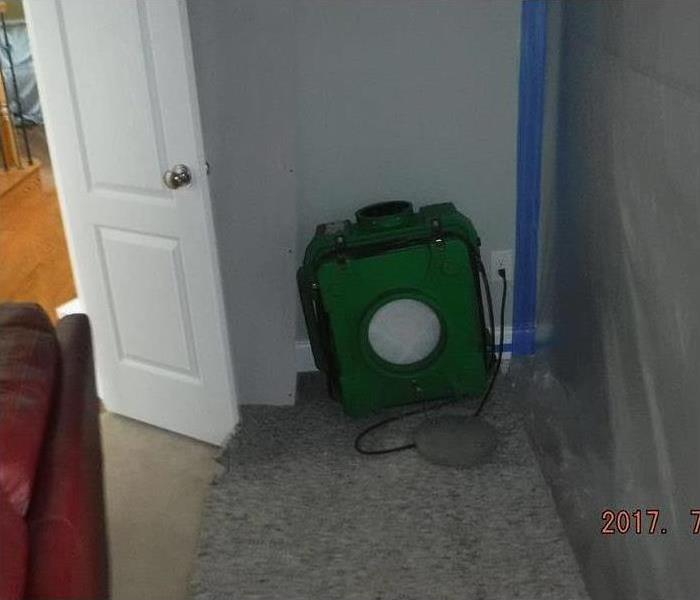 Air scrubber connected to a wall and plastic sheeting to contain mold